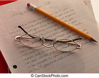 Language Arts - Childs eye glasses and pencil rest atop an...