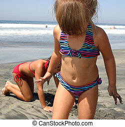 Beach Fun - Two young children playing in the sand