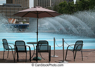 Awaiting YOU - Chairs and table by water fountain