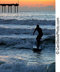 Sunset Surfer - A surfer catches a wave on a beach in San...