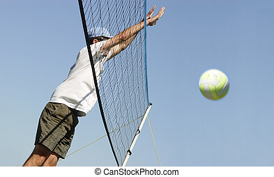 Volleyball - Young man hitting the ball over the net