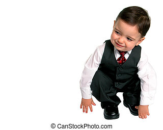 Little Man Squating - Toddler boy in 3 piece suit bends down...