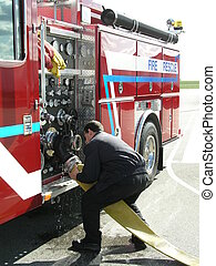 Handling hose - firefighter hooking up large diameter hose...