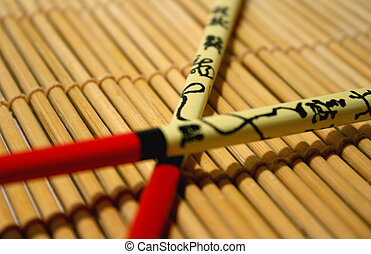 ChopsticksonBamboo - Two colorful chopsticks on a bamboo mat...