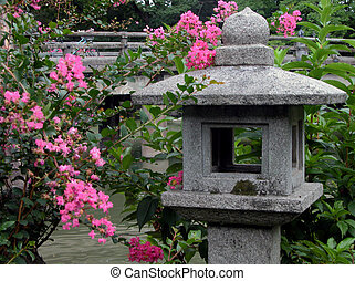 Lantern and flowers - A Japanese garden contianing a stone...