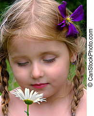 pretty smells - child smelling a daisy