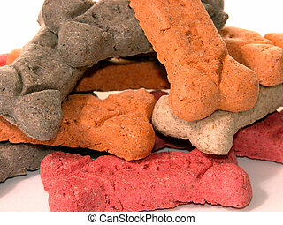 Dog Biscuits - Pile of bone shaped orange, brown and tan...