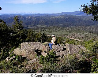Little Mac Gulch - Hiker sitting on a ledge overlooking...