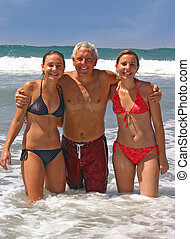 Lucky Man - A man standing in the ocean with two young woman...