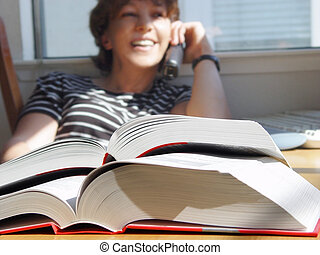 Big books - Girl is doing her homework and talking on the...