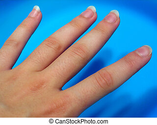 Fingers - Woman's fingers against a bright blue surface
