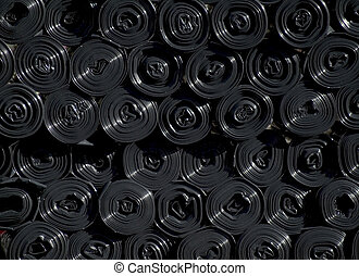 Black plastic bags - Stock of rolls of black plastic waste...