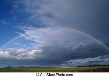 Rainbow - Almost complete rainbow over flat farmland in...