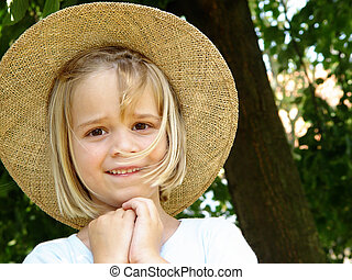 girl with straw hat - portrait of a 6 year old girl with...