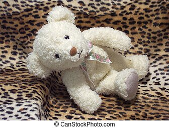 Teddy Bear - A fuzzy teddy bear laying on faux leopard skin...