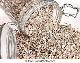 Spilled Oats v1 - Glass jar of full of raw oats spilt over...