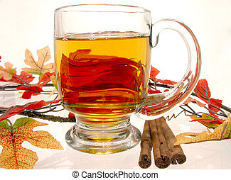 Hot Apple Cider - Glass mug of hot apple cider surrounded by...