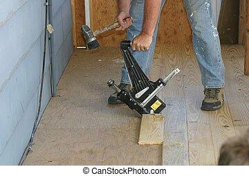 Nailing Floor Board - Man using special hammer to nail...