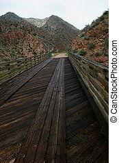 Old Wooden Bridge - Old wood plank bridge over stream on...