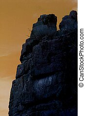 Solid Rock - Granite cliff is silhouetted against evening...