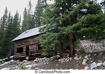 Log Cabin - Vintage log cabin sits precariously on...