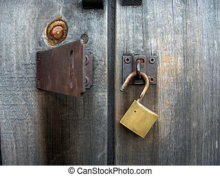 Open Lock - Brass pad lock and latch on old barn door