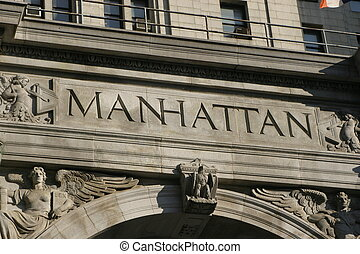 Manhattan engraved in stone on a buidling in financial...