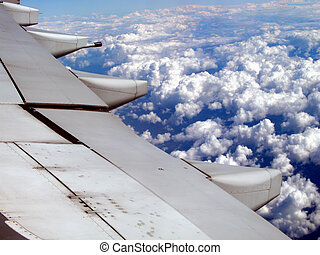 Wing - A airplane wing flying at high altitude above the...