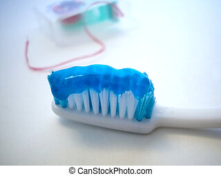 tooth brush with past and dental floss focus on tooth brush