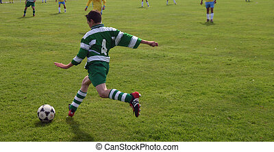 kicking the ball - youth playing football or soccer