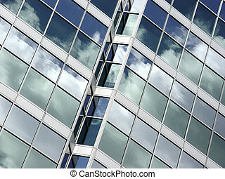 Blue sky and clouds reflected in the glass building in...