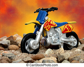 Dirt Bike - Toy dirt bike in sand and rock on a studio...
