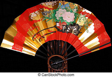 Red Japanese fan - A red Japanese fan on a bamboo support.