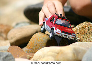 Playtime fun - boy pushing truck over rocky terrain - focus...