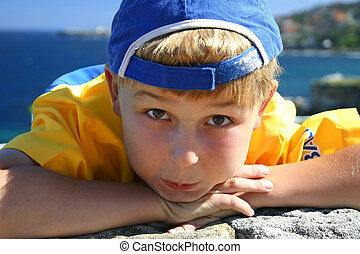 Scallywag - Boy with cap turned backwards, coastal backdrop
