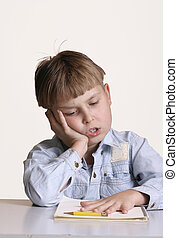 Schoolwork's boring - Child looking a little bored with it...