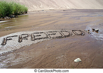 Freedom - The word freedom carved into the sandy streambed...