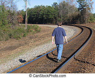 teen walking tracks - teen boy walking on railroad tracks in...