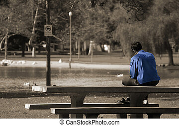 Feeling Blue - A man sitting alone on a picnic bench in the...