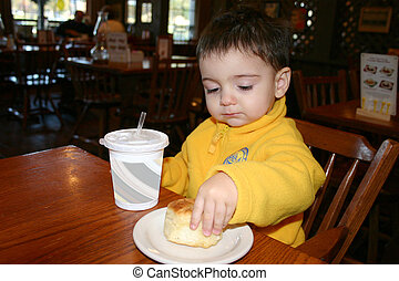 Boy Eating - Small boy eating a biscuit at a resturant
