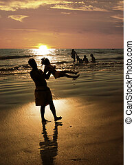 Beach at sunset - Father playing with his daughter on the...