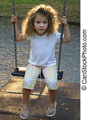 golden light - little girl swinging in a golden light