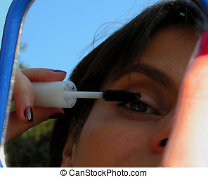 Make up - A woman applying mascara on her eyelashes-mirror...