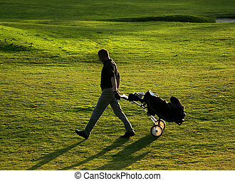 Golfer at dusk - Golf player on final tee