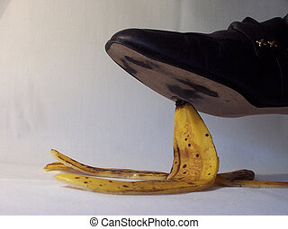 Banana slip - Foot shoe above banana peel, on a whitegray...