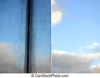 Sky reflection on stainless steel postument.