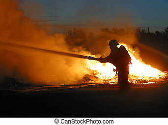 firefighter at work - A lone firefighters battles a blaze