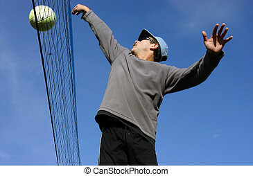 Beach Volleyball - Young man hitting the ball over the net