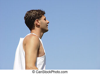 Young man against the blue sky