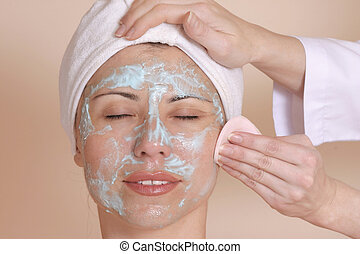Beauty Therapy - A beautician cleanses a woman's face.